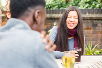 Friends in beer garden at table enjoying a drink, smiling 11015276497| 写真素材・ストックフォト・画像・イラスト素材|アマナイメージズ
