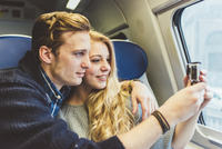 Young couple photographing through train carriage window, Italy 11015287400| 写真素材・ストックフォト・画像・イラスト素材|アマナイメージズ