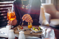 Cropped shot of young woman staying in boutique hotel eating aperitif 11015288794| 写真素材・ストックフォト・画像・イラスト素材|アマナイメージズ