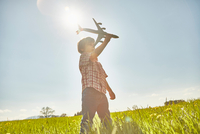 Boy in sunlit field with blue sky playing with toy airplane 11015289075| 写真素材・ストックフォト・画像・イラスト素材|アマナイメージズ