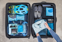 Overhead view of man's hands packing suitcase with walking boots, bike helmet, backpack, retro camera and blue shirt 11015295428| 写真素材・ストックフォト・画像・イラスト素材|アマナイメージズ