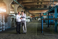 Colleagues conferring in tyre manufacturing plant, Ballenstedt, Germany 11015296579| 写真素材・ストックフォト・画像・イラスト素材|アマナイメージズ