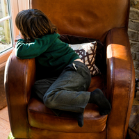 Boy relaxing on arm chair after school 11015296618| 写真素材・ストックフォト・画像・イラスト素材|アマナイメージズ