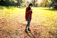 Young woman standing in park, using smartphone 11015298126| 写真素材・ストックフォト・画像・イラスト素材|アマナイメージズ