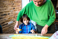 Mother helping son spread glue on crepe paper to make pinata 11015298478| 写真素材・ストックフォト・画像・イラスト素材|アマナイメージズ