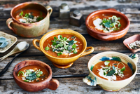 Bowls of garnished soup on wooden table 11015298534| 写真素材・ストックフォト・画像・イラスト素材|アマナイメージズ