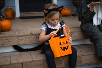 Girl in cat costume peering into trick or treating bag on porch stairway 11015300533| 写真素材・ストックフォト・画像・イラスト素材|アマナイメージズ
