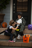 Boy and sister trick or treating in cat and pilot costume sitting on stairway looking in bags 11015300534| 写真素材・ストックフォト・画像・イラスト素材|アマナイメージズ