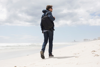 Rear view of young man strolling alone on beach, Western Cape, South Africa 11015302563| 写真素材・ストックフォト・画像・イラスト素材|アマナイメージズ