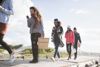 Row of young adult friends strolling along beach boardwalk reading smartphones, Western Cape, South Africa 11015302590| 写真素材・ストックフォト・画像・イラスト素材|アマナイメージズ