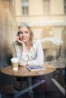 Mid adult woman with digital tablet in cafe window seat 11015303881| 写真素材・ストックフォト・画像・イラスト素材|アマナイメージズ