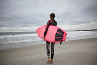 Rear view of female surfer carrying surfboard to sea on Rockaway Beach, New York, USA 11015304027| 写真素材・ストックフォト・画像・イラスト素材|アマナイメージズ