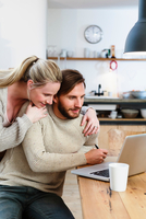 Mid adult couple looking at laptop in kitchen 11015305010| 写真素材・ストックフォト・画像・イラスト素材|アマナイメージズ