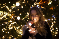 Young woman with lights in her hand, tree in background 11015305121| 写真素材・ストックフォト・画像・イラスト素材|アマナイメージズ