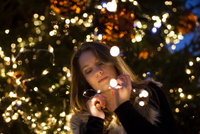 Young woman looking at lights in her hand, tree in background 11015305122| 写真素材・ストックフォト・画像・イラスト素材|アマナイメージズ