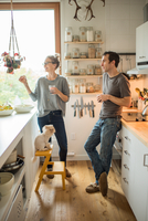 Mid adult couple with red wine chatting in kitchen 11015309472| 写真素材・ストックフォト・画像・イラスト素材|アマナイメージズ