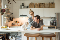 Mid adult couple with cat at kitchen counter 11015309473| 写真素材・ストックフォト・画像・イラスト素材|アマナイメージズ