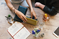 Young woman opening purse at cocktail bar table 11015309520| 写真素材・ストックフォト・画像・イラスト素材|アマナイメージズ