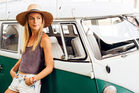 Woman leaning against vintage camper van looking away 11015309700| 写真素材・ストックフォト・画像・イラスト素材|アマナイメージズ