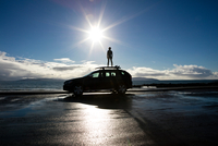 Boy standing on surf board on top of a car, looking out to sea 11015313392| 写真素材・ストックフォト・画像・イラスト素材|アマナイメージズ