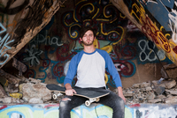 Portrait of young male skateboarder sitting on graffiti wall at ruined mine 11015313489| 写真素材・ストックフォト・画像・イラスト素材|アマナイメージズ