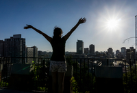 Woman with arms raised looking at view of Santiago de Chile, Chile 11015316796| 写真素材・ストックフォト・画像・イラスト素材|アマナイメージズ