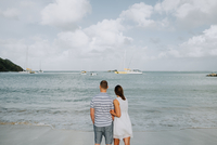 Couple standing, looking out to sea, rear view, Saint Martin, Caribbean 11015317254| 写真素材・ストックフォト・画像・イラスト素材|アマナイメージズ
