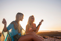 Two young women sitting on beach at sunset, playing ukulele, Cape Town, South Africa 11015318278| 写真素材・ストックフォト・画像・イラスト素材|アマナイメージズ