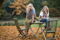 Portrait of two sisters sitting on patio table in autumn garden 11015318396| 写真素材・ストックフォト・画像・イラスト素材|アマナイメージズ