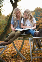 Portrait of two sisters sitting on patio table reading book in autumn garden 11015318397| 写真素材・ストックフォト・画像・イラスト素材|アマナイメージズ