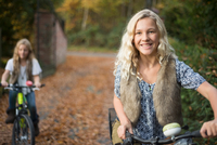 Portrait of two sisters cycling in autumn park 11015318404| 写真素材・ストックフォト・画像・イラスト素材|アマナイメージズ