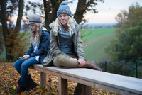 Portrait of girl and her sister sitting on autumn park bench 11015318417| 写真素材・ストックフォト・画像・イラスト素材|アマナイメージズ