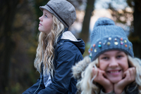 Portrait of girl and her sister in rural landscape wearing knit hat 11015318418| 写真素材・ストックフォト・画像・イラスト素材|アマナイメージズ