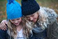 Blond haired sisters wearing knit hats looking down in garden 11015318422| 写真素材・ストックフォト・画像・イラスト素材|アマナイメージズ