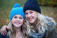 Portrait of blond haired sisters wearing knit hats in garden 11015318423| 写真素材・ストックフォト・画像・イラスト素材|アマナイメージズ