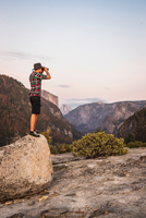 Man standing on boulder looking through binoculars, Yosemite National Park, California, USA 11015318812| 写真素材・ストックフォト・画像・イラスト素材|アマナイメージズ