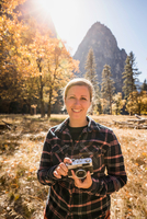 Portrait of woman holding camera in autumn landscape, Yosemite National Park, California, USA 11015318817| 写真素材・ストックフォト・画像・イラスト素材|アマナイメージズ