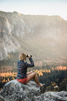 Woman sitting on boulder looking out through binoculars, Yosemite National Park, California, USA 11015318826| 写真素材・ストックフォト・画像・イラスト素材|アマナイメージズ