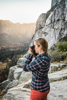 Woman photographing landscape from rock formation, Yosemite National Park, California, USA 11015318827| 写真素材・ストックフォト・画像・イラスト素材|アマナイメージズ