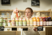 Woman in shop looking at smoothies 11015319093| 写真素材・ストックフォト・画像・イラスト素材|アマナイメージズ