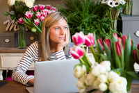 Florist worker in flower shop, using laptop, bored expression 11015319623| 写真素材・ストックフォト・画像・イラスト素材|アマナイメージズ