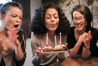 Woman blowing out candles on birthday cakes 11015319752| 写真素材・ストックフォト・画像・イラスト素材|アマナイメージズ