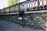 Young female BMX cyclist looking over her shoulder from wall on cobbled street 11015319796| 写真素材・ストックフォト・画像・イラスト素材|アマナイメージズ