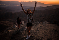 Portrait of young woman with hands raised in Joshua Tree National Park at sunset, California, USA 11015320519| 写真素材・ストックフォト・画像・イラスト素材|アマナイメージズ