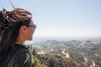Young woman looking out at landscape from Hollywood sign, Los Angeles, California, USA 11015320521| 写真素材・ストックフォト・画像・イラスト素材|アマナイメージズ