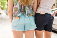 Two female friends, outdoors, smartphones in back pockets, mid section, rear view 11015320883| 写真素材・ストックフォト・画像・イラスト素材|アマナイメージズ