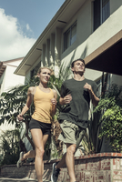 Young couple jogging in street, low angle view 11015325025| 写真素材・ストックフォト・画像・イラスト素材|アマナイメージズ