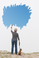 Senior woman with dog on lead painting blue sky in air 11015325492| 写真素材・ストックフォト・画像・イラスト素材|アマナイメージズ