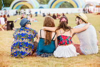 Rear view of friends sitting on grass at festival 11015325856| 写真素材・ストックフォト・画像・イラスト素材|アマナイメージズ