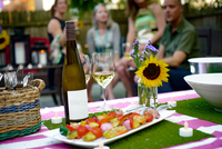 Group of people at garden party, bottle of wine and vegetable kebabs in foreground 11015326085| 写真素材・ストックフォト・画像・イラスト素材|アマナイメージズ
